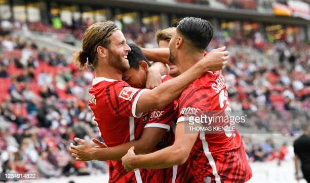 Freiburg's South Korean midfielder Jeong Woo-yeong celebrates scoring the 0-1 with German forward Lucas Hoeler and Italian midfielder Vincenzo Grifo...