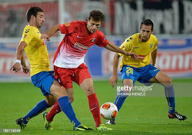 Freiburg's Swiss forward Admir Mehmedi vies for the ball with Estoril's defender Goncalo and defender Ruben Fernandes during the UEFA Europa League...