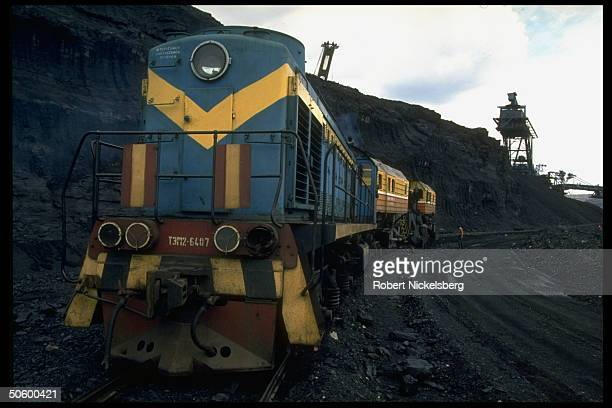 Freight car carrying extracted ore along track cut into 1 of world's largest open pit coal mines operating terrain in Central Steppes region Ekibastuz