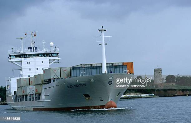 a freight container ship navigates its way along motlawa river. - motlawa river stock pictures, royalty-free photos & images