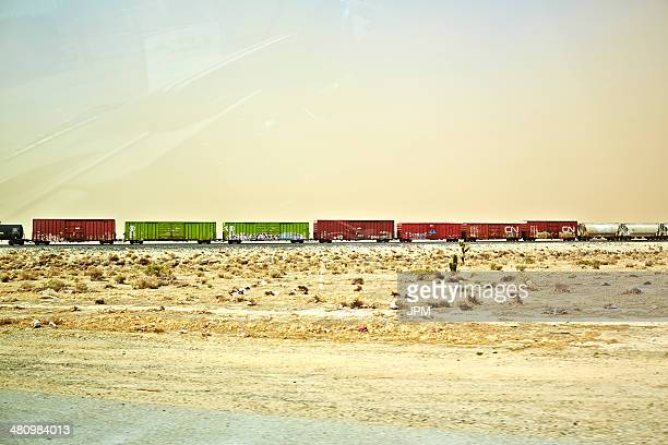 freight locomotive moving through arid landscape, california, usa - cargo train stock photos and pictures