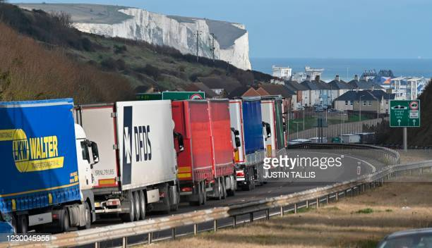 Freight lorries queue on the main route into the port of Dover on the south coast of England on December 10, 2020. - Big queues of lorries snaked...
