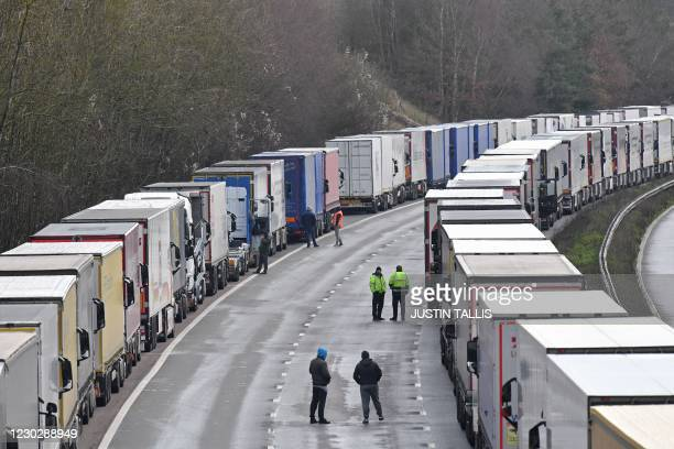 Freight lorries remain queued up on the M20 motorway, southbound, leading to the Port of Dover at Mersham in south east England on December 24 as...