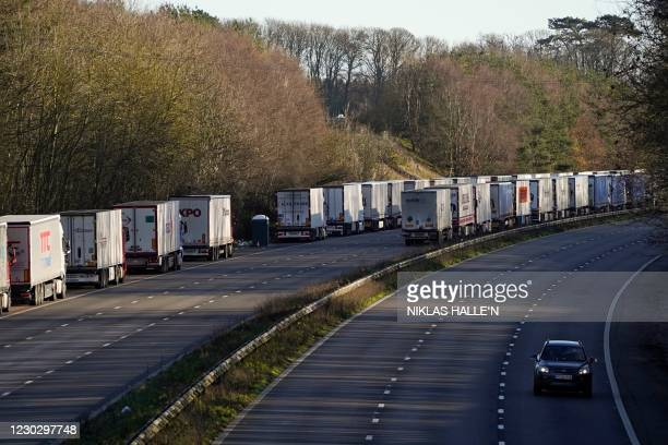 Freight lorries remain queued up on the M20 motorway, southbound, leading to the Port of Dover, at Ashsford, in south-east England, on December 25 as...