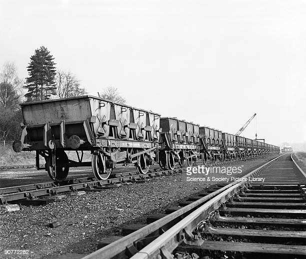 Freight train carrying stone at Stansted goods yard waiting to be unloaded by crane The wagons were specially built to carry four narrowgauge tipper...