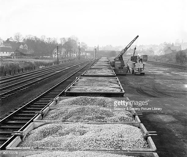 Freight train carrying stone at Stansted goods yard. Workers can be seen unloading the stone to a lorry, through the use of a crane. Heavy loads were...