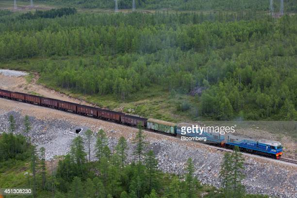 A freight train draws rail wagons through the taiga forest towards the Elga coal complex operated by OAO Mechel near Elga Sakha Republic Russia on...
