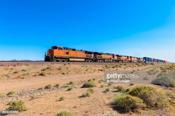 freight train driving through mojave desert california - cargo train stock photos and pictures