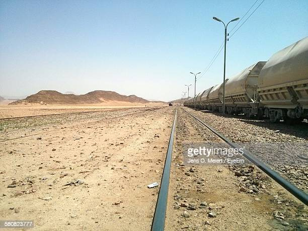 Freight Train On Barren Landscape Against Clear Blue Sky