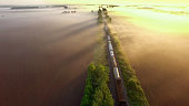 Freight train rolls across surreal, foggy landscape at sunrise