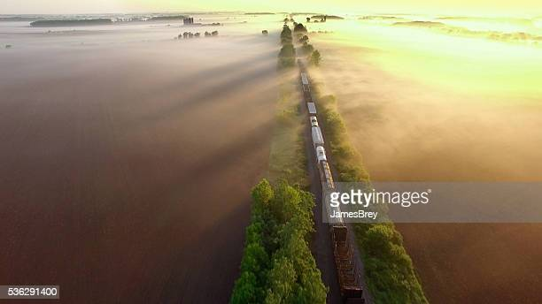 Freight train rolls across surreal, foggy landscape at sunrise