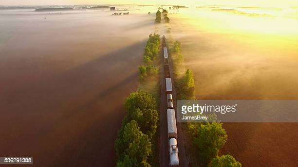 Freight train rolls through fog, across breathtaking landscape at sunrise.