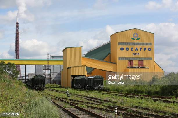 A freight train transporting phosphate fertilizer passes a storage warehouse at the PhosAgroCherepovets fertilizer plant operated by PhosAgro PJSC in...