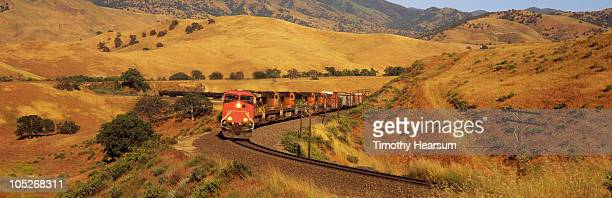 freight train winding through golden hills - timothy hearsum photos et images de collection