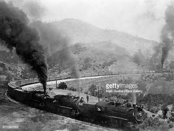 Freight train winding through mountains, late 1900s.