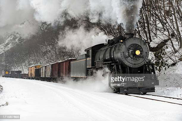 freight train with steam locomotive smoke in cold winter snow - locomotive stock photos and pictures