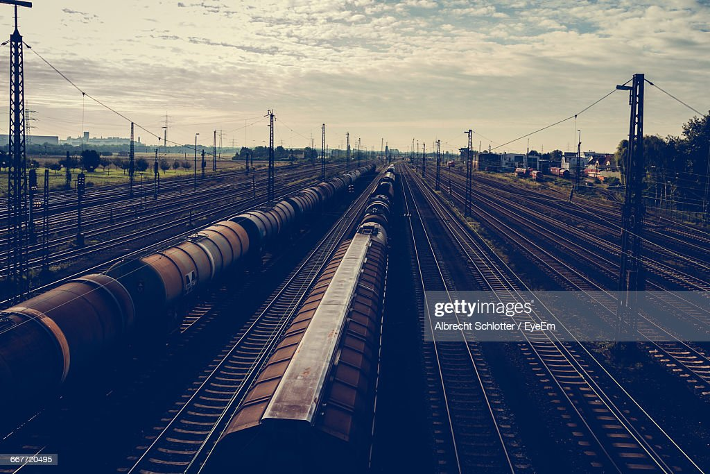 Freight Trains On Railroad Tracks Against Sky During Sunset : Stock-Foto