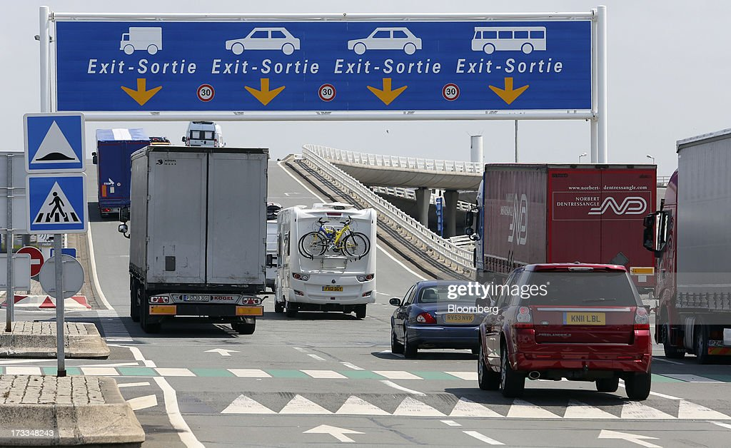 Freight trucks and automobiles leave the Port of Calais after arriving by ferry in Calais, France, on Thursday, July 11, 2013. Eurotunnel was barred by the U.K. Competition Commission from operating a ferry service between France and Dover in the U.K. on concern it would give it too much dominance on the Channel traffic route. Photographer: Chris Ratcliffe/Bloomberg via Getty Images
