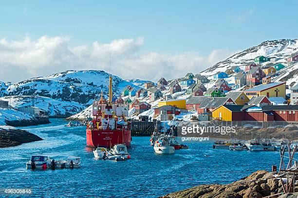 freight vessel approaching a small harbour in greenland - greenland stock pictures, royalty-free photos & images