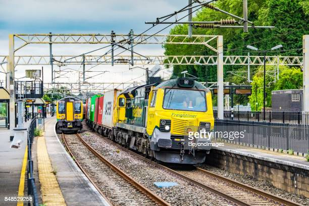 freightliner container train passes london midland commuter service - rail freight stock pictures, royalty-free photos & images