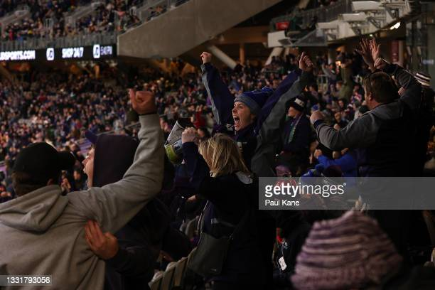 Fremantle fans celebrate winning the round 20 AFL match between Fremantle Dockers and Richmond Tigers at Optus Stadium on August 01, 2021 in Perth,...