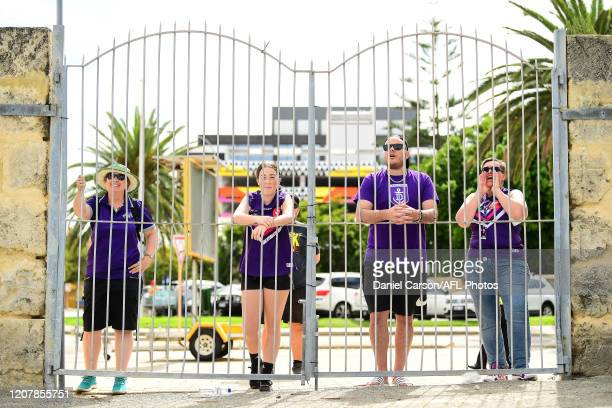 Fremantle fans cheers on through the locked fence during the 2020 AFLW Semi Final match between the Fremantle Dockers and the Gold Coast Suns at...