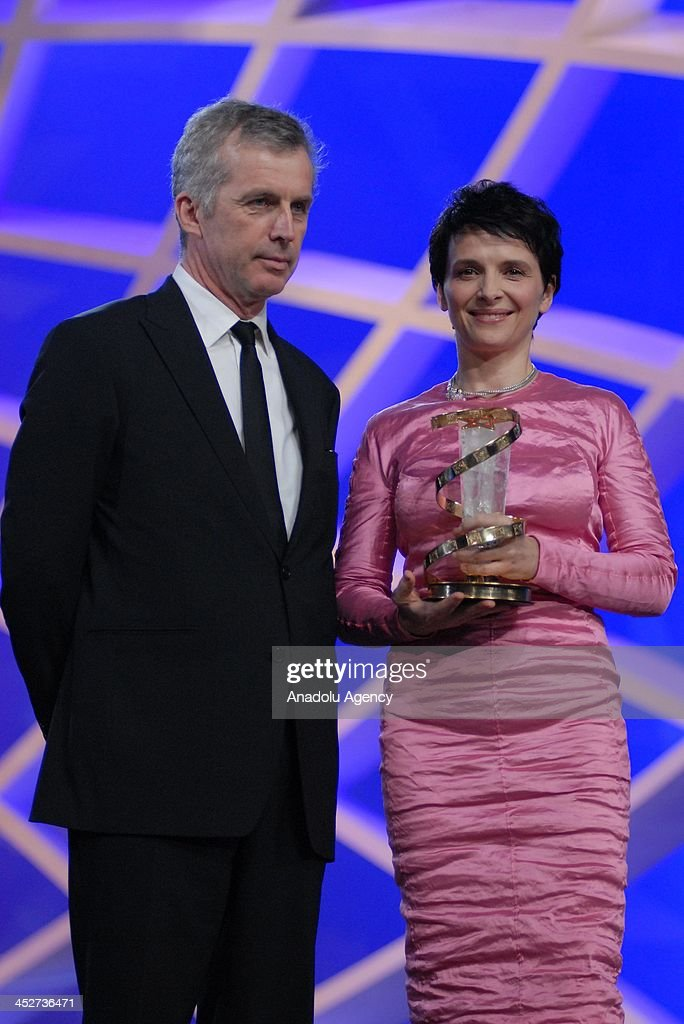 French actess Juliette Binoche (R) receives a special honor award from French film director Bruno Dumont at the 13th Marrakech International Film Festival in Morocco on December 1, 2013.