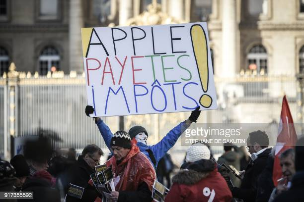 French activist JeanBaptiste Redde aka Voltuan holds a placard reading Apple pay your taxes as activists of the Association for the Taxation of...