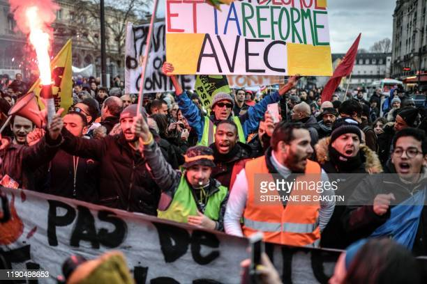 French activist Jean-Baptiste Redde aka Voltuan , holds a placard as he takes part in a demonstration of rail workers and employees of Paris' RATP...