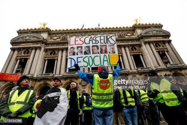 French activist JeanBaptiste Redde aka Voltuan holds a placard reading 'the social destroyers' and picturing French Minister of Public Action and...