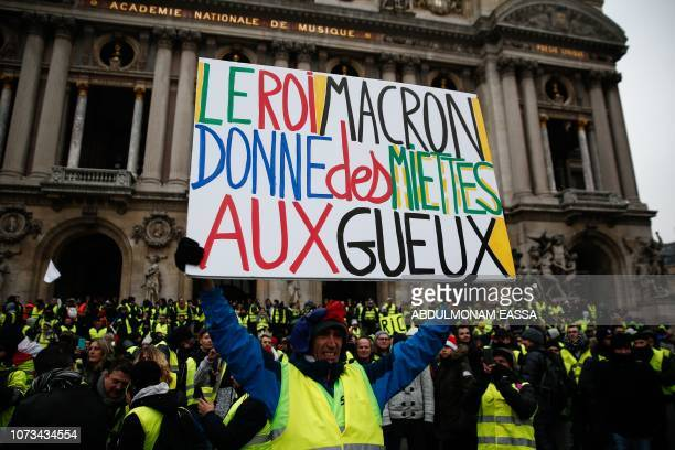French activist JeanBaptiste Redde aka Voltuan wearing a yellow vest holds a cardboard reading 'The King Macron gives crumbs to the beggars' during a...