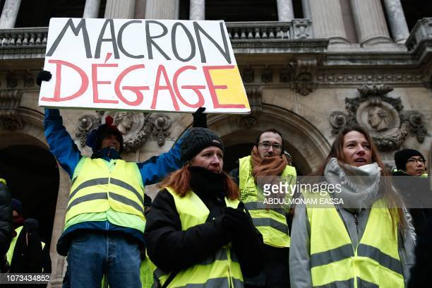 French activist JeanBaptiste Redde aka Voltuan wearing a yellow vest holds a cardboard reading 'Macron go away' during a demonstration in front of...