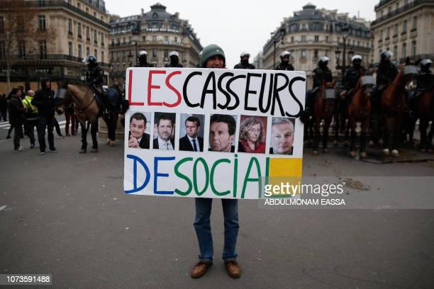 French activist JeanBaptiste Redde aka Voltuan wearing a yellow vest poses with a cardboard reading 'Macron go away' during a demonstration in front...