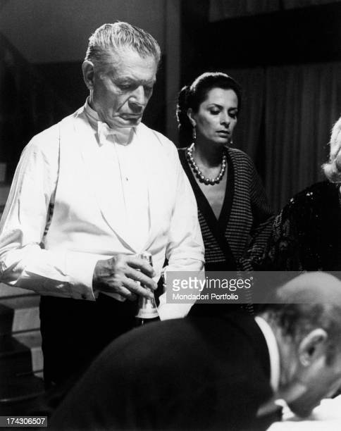 French actor Alain Cuny holding a bottle of champagne and French actress Juliette Mayniel looking down in I prosseneti Rome 10th October 1975