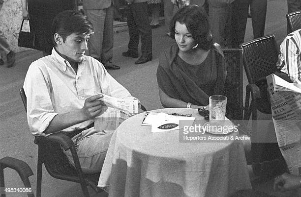 French actor Alain Delon and Germanborn French actress Romy Schneider sitting at the table of a cafà© on Via Veneto and reading a paper Rome
