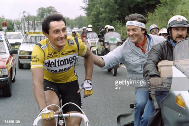 French actor Alain Delon encourages Italian Giuseppe Saronni during the 7th stage of the 74th Tour de France cycling race run between Epinal and...