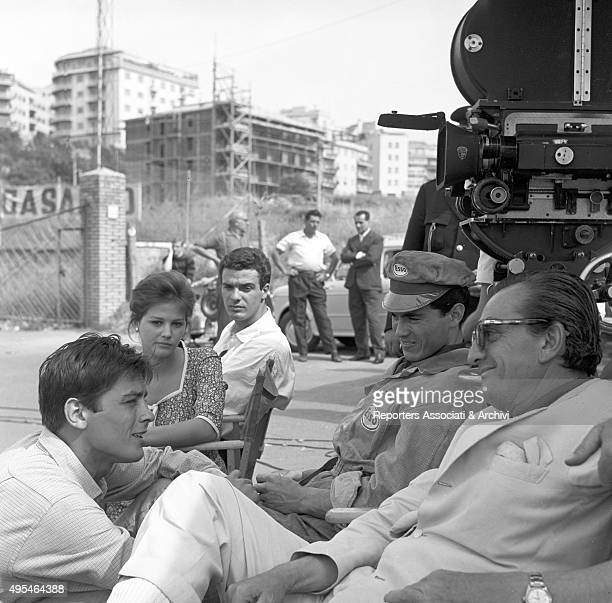 French actor Alain Delon Italian actress Claudia Cardinale French actor Max Cartier and Italian director Luchino Visconti having a break on the set...