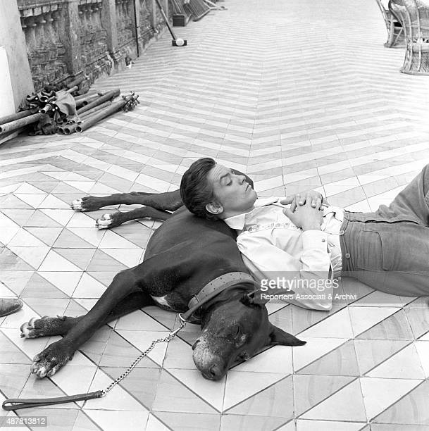 French actor Alain Delon pausing on the set of The Leopard directed by Italian director Luchino Visconti Lying on the floor resting his head on a...