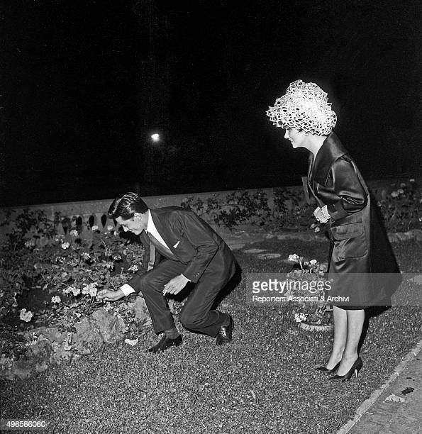 French actor Alain Delon picking up a flower in the the flowerbed at the party in a villa in Grottaferrata Roma Castles with many actors included...