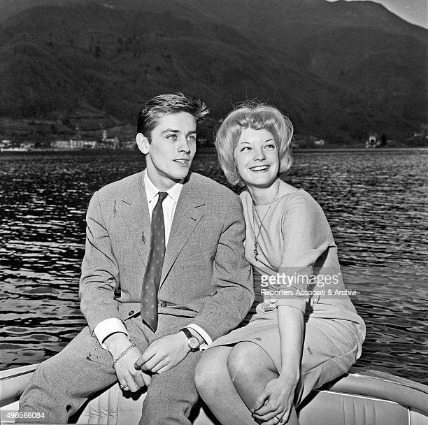 French actor Alain Delon sitting in a boat on the Lake Lugano with German actress Romy Schneider at their engagement party in Vico Morcote a village...