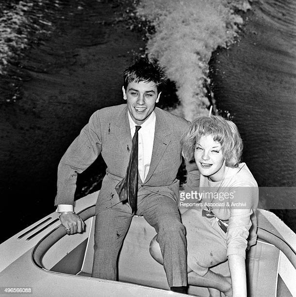 French actor Alain Delon sitting in a motorboat with German actress Romy Schneider at their engagement party in Vico Morcote a village of Canto of...