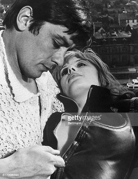 French actor Alain Delon zips Marianne Faithfull's leather jacket in a scene from their movie Girl on a Motorcycle