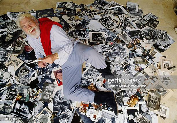 French actor and artist Jean Marais stretches out on a pile of photographs at his home in Vallauris France