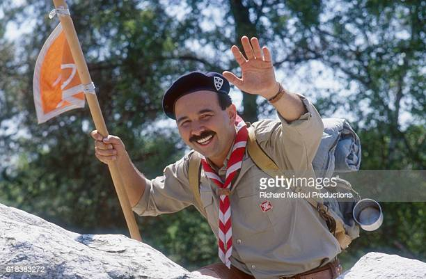 French actor and director Gérard Jugnot wears a scout uniform on the set of his 1985 film Scout Toujours The French film directed by Jugnot also...