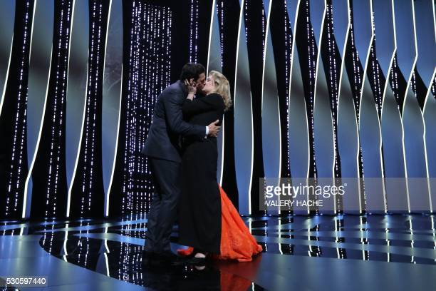 TOPSHOT French actor and Master of Ceremony Laurent Lafitte kisses French actress Catherine Deneuve on May 11 2016 during the opening ceremony for...