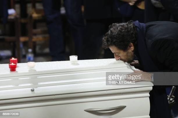 French actor and singer Patrick Bruel kisses the coffin during the funeral ceremony of late French singer Johnny Hallyday at the Eglise de la...