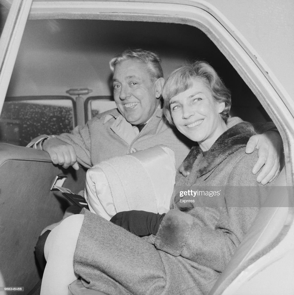 French actor and writer Jacques Tati (1907-1982) pictured sitting together with his wife Micheline Winter in the back seat of a car at London airport on 11th April 1966.