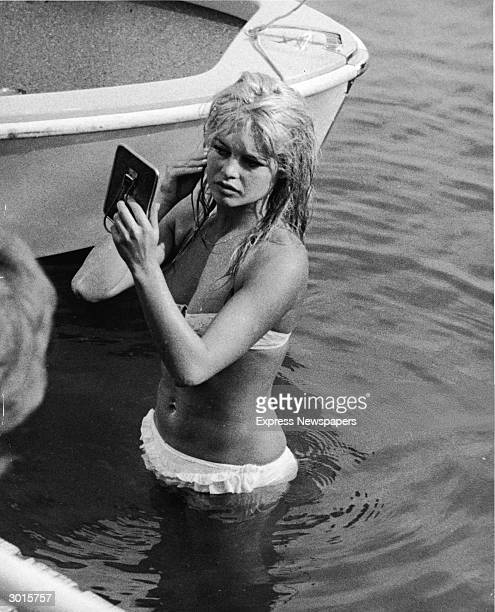 French actor Brigitte Bardot looks at her reflection in a mirror, while standing in the waters of Lake Leman, June 13, 1961.