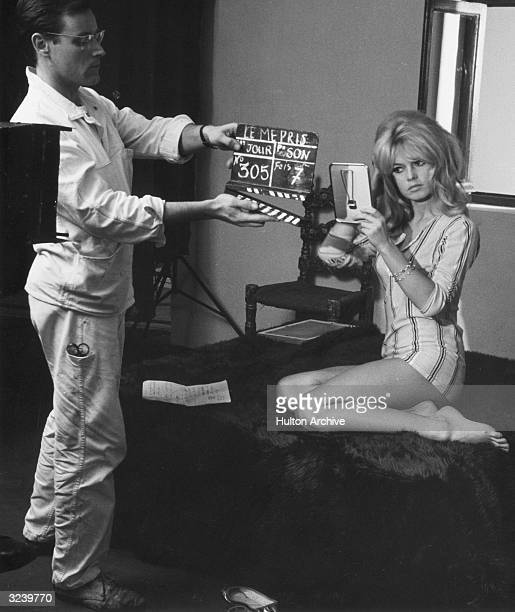 French actor Brigitte Bardot uses a mirror while a crew member holds the clapperboard in front of her on the set of director JeanLuc Godard's film...