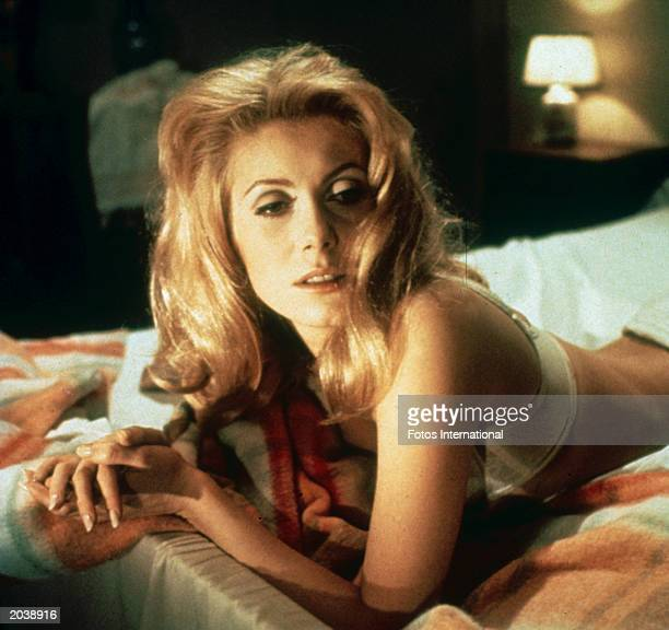 French actor Catherine Deneuve as Severine Serizy lies on a bed on her stomach in a still from the film 'Belle de Jour' directed by Luis Bunuel 1967